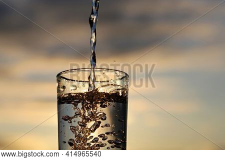 Clean Water Pouring Into Drinking Glass On Sunset Blurred Background. Concept Of Health And Freshnes