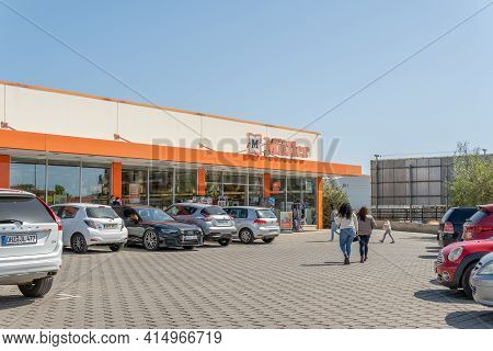 Campos, Spain; March 28 2021: Main Facade And Parking Area With Parked Vehicles Of A Store Of The Ge