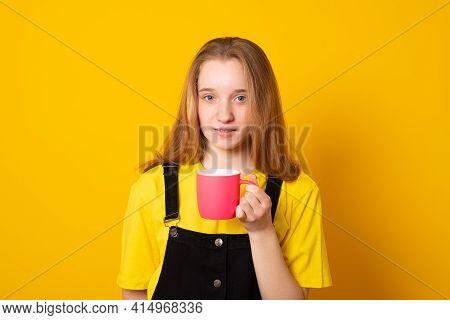 Cute Young Girl Holding A Pink Mug. Stylish Teen Girl Drinking From A Pink Mug.