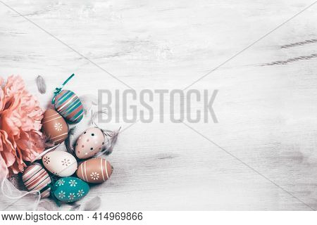 Easter banner with eggs and feathers on a wooden background. The minimal concept of Easter. Top view. An Easter card with a copy of the place for the text.