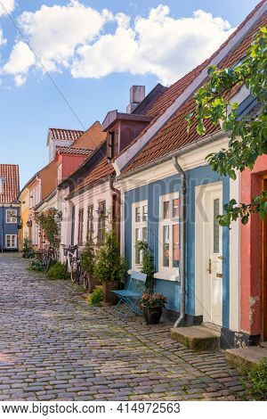 An idyllic cobbled street with colorful houses at the old town of Aalborg, Denmark