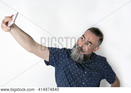 40-45-year-old Man With A Large, Medium-gray Beard Using His Smart Phone To Take A Self-portrait (se
