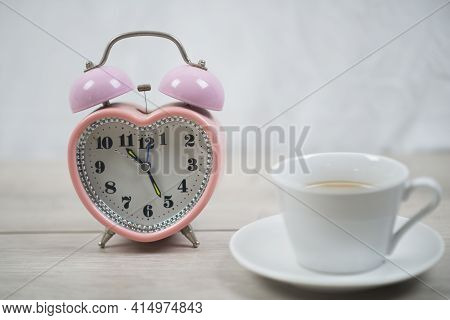 Alarm Clock And Cup Of Coffee. Still Life Concept With Pink Alarm Clock And Cup Of Coffee On White T