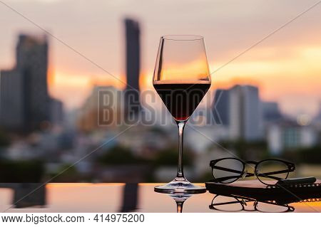A Glass Of Red Wine With Spectacles And Notebook Put On Table With City Background. Stay Home Concep