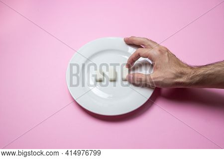 Sugar On A Pink Background. Three Cubes Of Sugar On A White Plate. The Hand Reaches For The Sugar.