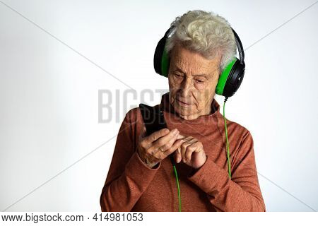 Older Woman Listening To Music With Headphones And Smartphone. Looking At Phone Screen Using Mobile