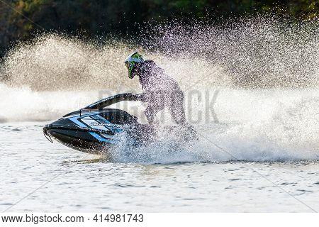 Krasnodar, Russia - October 24, 2020: Jet Ski Superjet Racer Drives Watercraft Splashing In Sunset W