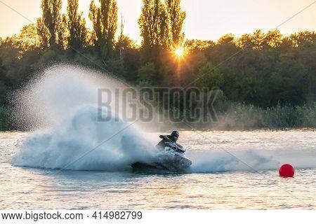 Krasnodar, Russia - October 24, 2020: Jet Ski Racer Drives Watercraft Splashing In Sunset While Raci