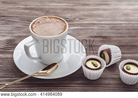 A Cup Of Cappuccino And Praline Candies.