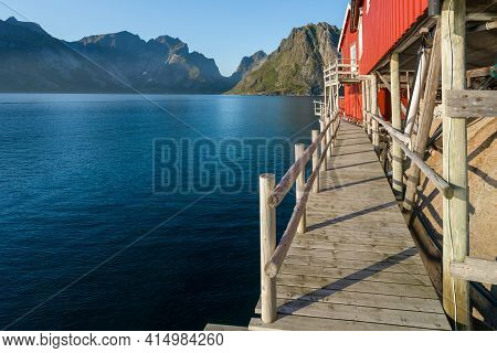 Wooden Walk Under Red Wooden Fishermans House In Reine, Lofoten, Norway. Sunset Of A Sunny Day In Th