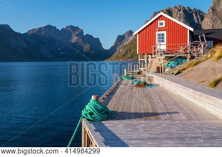 Red Wooden Fishermans House In Reine, Lofoten, Norway. Sunset Of A Sunny Day In The Village By The S