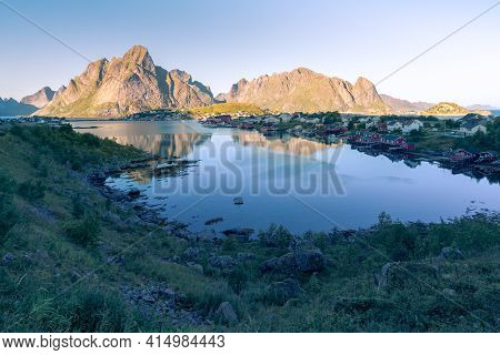 Village Of Reine In Lofoten In The Golden Hour During Sunset. Rocks And The Village Reflect On The W