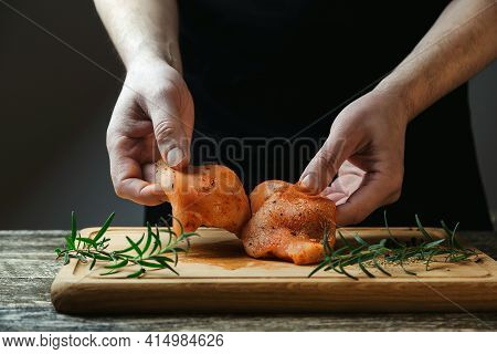 Chef Cooking Chicken Fillet With Herbs And Spices On Wooden Board. Cooking Tasty Hot Meal. Raw Chick
