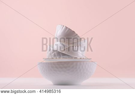 White Ceramic Crockery Stack With Golden Bezel, Different Texture On White Wooden Table, Pastel Pink
