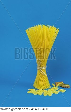 Raw Spaghetti And Pasta On A Blue Background. Spaghetti And Pasta As Background With Space For Text.