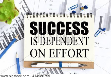 Success Is Dependent On Effort. Text On White Notepad Paper On A Light Background Near Financial Cha