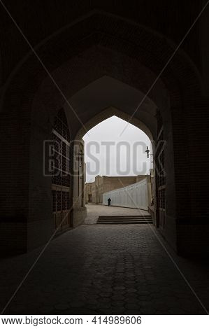 A Fragment Of An Old Street. An Ancient Brick Building With An Arch. View Through The Arch To The St