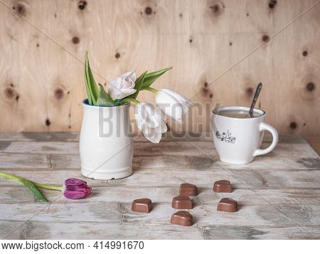Greeting Card With White Tulips In A White Mug And Chocolates And Tea In A White Dishware Room