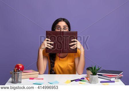 Shocked Woman In Eyeglasses Hiding Behind Book, Peeking Out