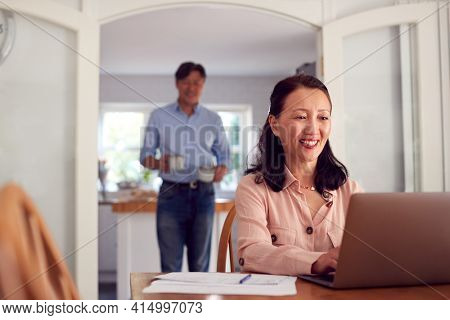 Mature Asian Couple At Home Using Laptop To Organise Household Bills And Finances