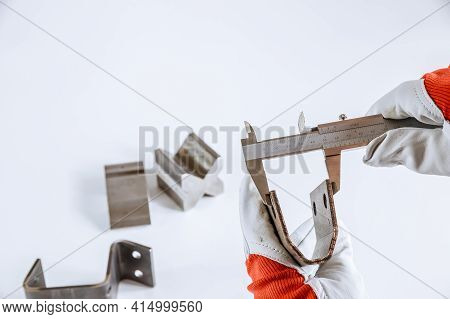 Precise Measurement Of Metal Parts On A White Background Using A Vernier Caliper