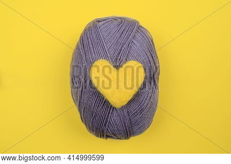 A Yellow Wool Heart Rests On A Gray Ball Of Knitting Thread.the Concept Of Handwork, Needlework And
