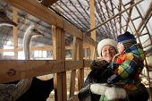 Granmother with toddler at ostrich farm in winter Tyumen Russia poster