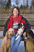 Vertical image of a woman sitting outdoors with her Standard Poodle and Miniature Australian Shepherd. Focus on woman's face. poster