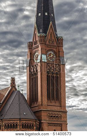 closeup of a red brick steeple with dramatic sky. poster