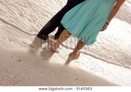 Male And Female Walking Along The Beach Close Up From Waist Down