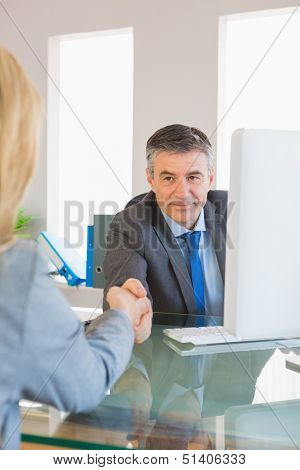 Amused mature businessman shaking the hand of a blonde interviewee in office