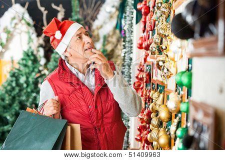 Senior man in Santa hat selecting Christmas ornaments at store