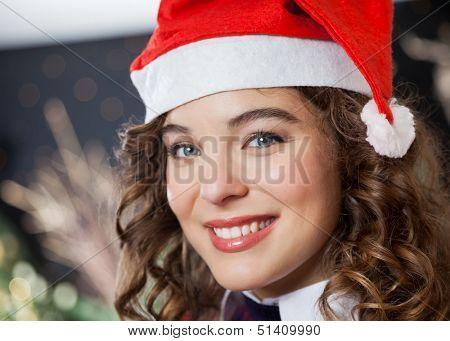 Closeup portrait of beautiful young woman wearing Santa hat in Christmas store