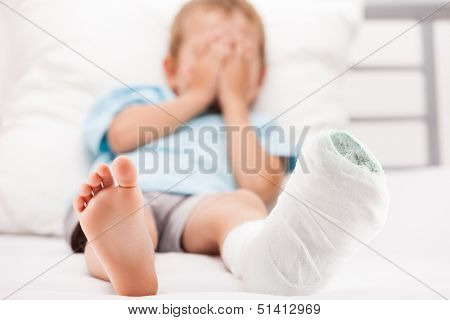 Human healthcare and medicine concept - little child boy with plaster bandage on leg heel fracture or broken foot bone