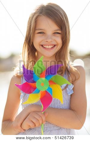 summer holidays, celebration, family, children and people concept - happy girl with colorful pinwheel toy