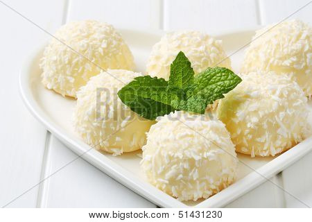 white chocolate bonbons with coconut, on a heart shaped plate