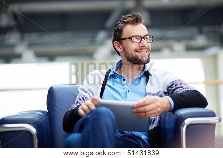 Smart businessman with touchpad thinking of new idea or strategy in office