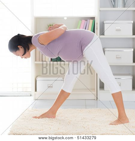 Prenatal yoga. Full length healthy 8 months pregnant calm Asian woman meditating or doing yoga exercise at home. Relaxation yoga forward bending pose.