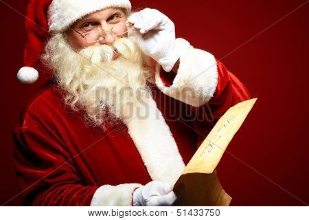 Portrait of happy Santa Claus holding Christmas letter in his hands and looking at camera