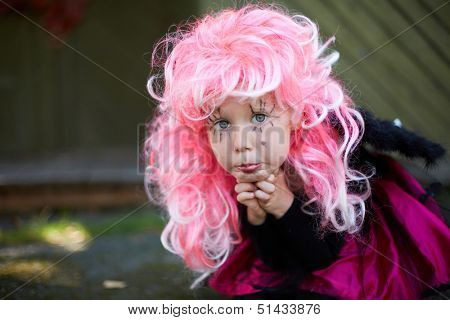 Portrait of cute girl in Halloween costume and pink wig looking at camera