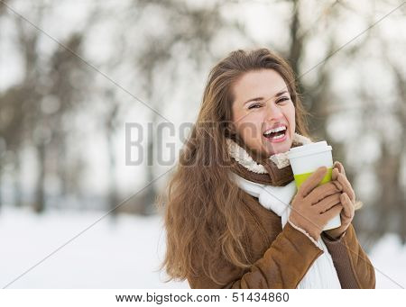 Smiling Young Woman With Cup Of Hot Beverage In Winter Park