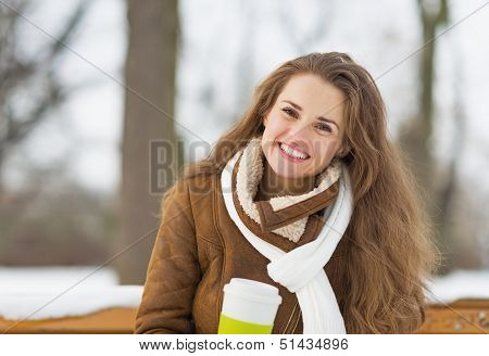 Happy Young Woman With Cup Of Hot Beverage Sitting On Bench In W