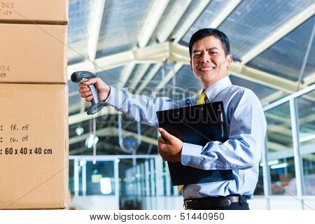 Young Indonesian man in a suit with a bar code scanner in a Asian warehouse