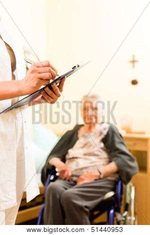 Young nurse and female senior in nursing home, measurements are taken or administrative duties taken care of