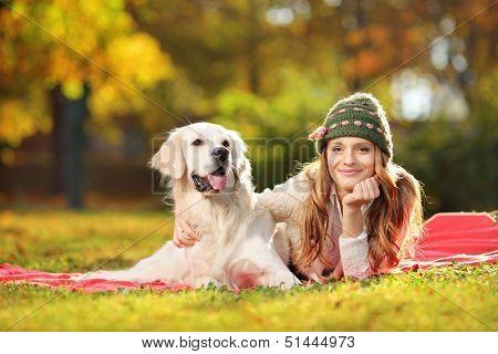 Pretty female lying down with her labrador retriever dog in a park