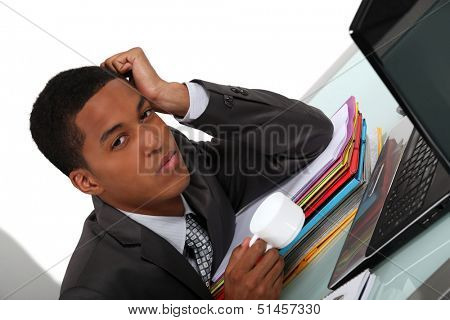 Tired young businessman with a coffee at his computer