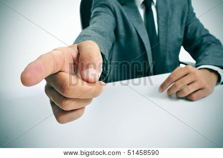 man wearing a suit sitting in a table pointing with the finger the way out
