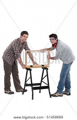Tradesmen building a wooden frame