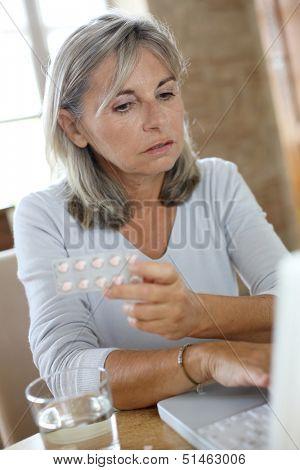 Senior woman reading medication instructions on internet