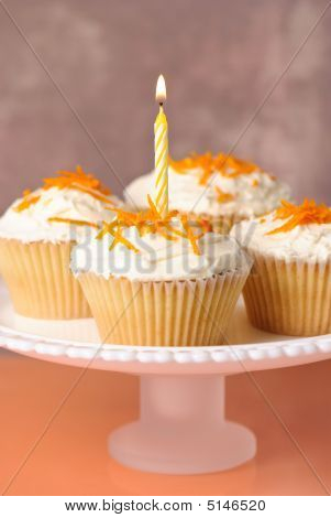 Comport of cupcakes with orange zest one cake with lit candle poster